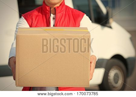 Young male courier with parcel, closeup