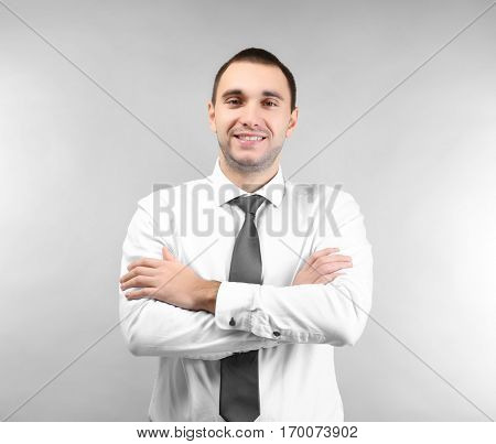 Handsome man with crossed arms on light background