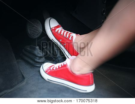 Female feet with brake and accelerator pedals