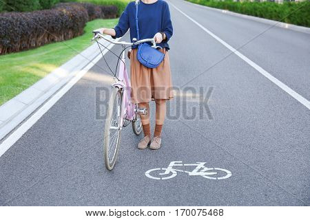 Young woman with bicycle standing on road near bikeway sign