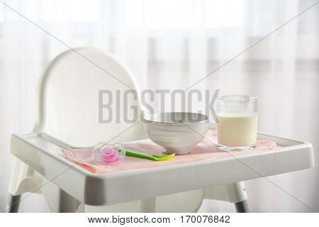 Highchair with healthy baby food at home. Child feeding concept