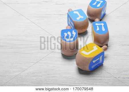 Dreidels for Hanukkah on light wooden table