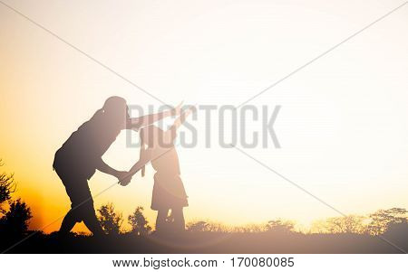 Silhouette of happy family mother and child playing outdoors at sunset