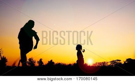Silhouette happy family mother and daughter in the park at sunset with sun flare Concept of friendly family and of summer vacation.