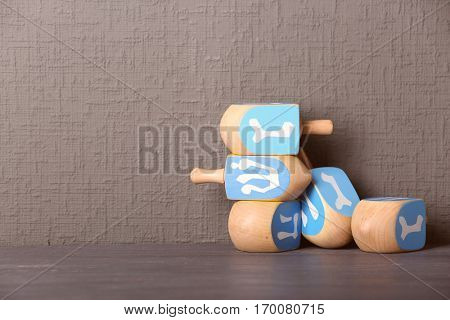 Dreidels for Hanukkah on wooden table against grey textured wall