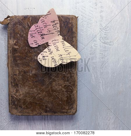 A square photo of an old book with a butterfly cut out of paper toned with watercolor, shot from above on a wooden board, with copyspace