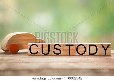 Word CUSTODY made of wooden blocks with toy car on table against blurred background, closeup
