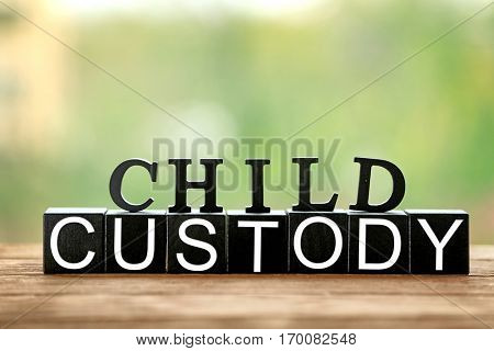 Text CHILD CUSTODY made of black blocks and letters on table against blurred background, closeup