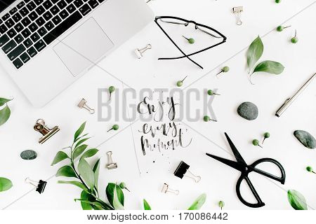 White office desk workspace with quote Enjoy Every Moment green leaves and office supplies. Laptop scissors glasses on white background. Flat lay top view.