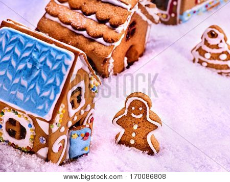 Street of gingerbread houses, top view. Gingerbread man and gingerbread Christmas Christmas Tree with glaze in deep snow. Christmas food concept.