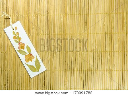 Handmade Dried Flower Bookmark on the Bamboo Background. Craft Art. Use For Texture and Wallpaper.