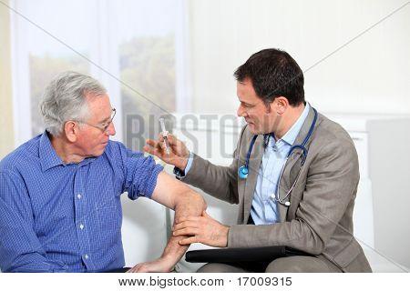 Läkare gör vaccination till äldre man