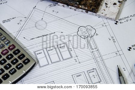 2d elevation of a new house plan with pencil, 2ds of a new exterior house construction plans on builders desk, close up of house plans with computer, house plan blueprints for a new housing development