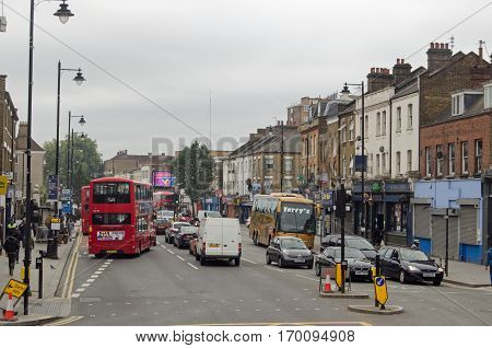 LONDON UK - SEPTEMBER 17 2016: Busy traffic and pedestrials using the famous Tottenham High Road on a cloudy day in North London.