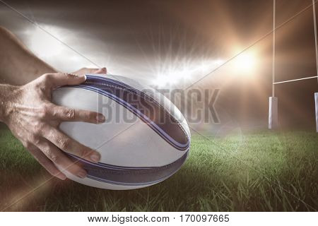 Close-up of of sports player holding ball against rugby pitch 3D