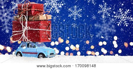 Retro toy car delivering Christmas or New Year gifts on festive blue background
