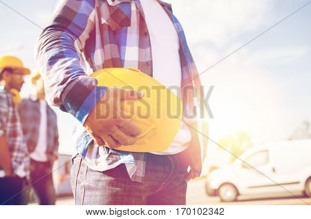 building, protective gear and people concept - close up of builder hand holding yellow hardhat or helmet at construction site