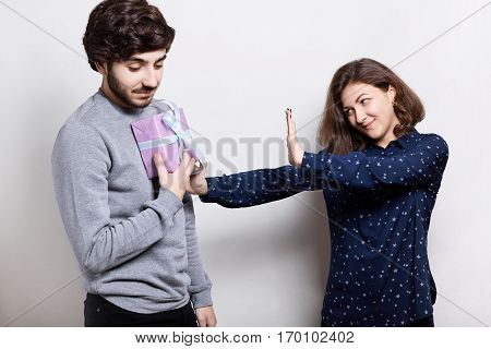 People and relationships. Young man giving offended woman gift box girl refusing to accept present. Couple having some problems in their relations. Girlfriend doesn`t want to take a present