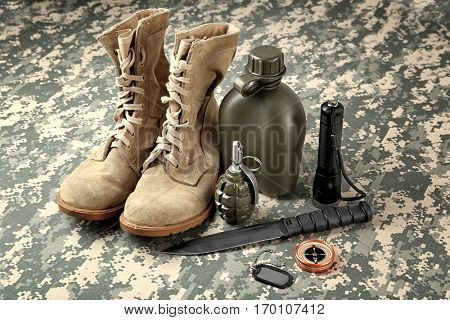 Set of military equipment and combat boots  on camouflage background