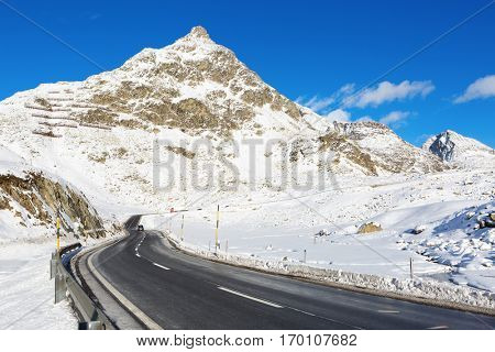 Mountain road in a sunny winter day (Swiss alps). Julier Pass, Graubunden, Switzerland.  Julier Pass - mountain pass in Switzerland, in the Albula Range of the Alps.