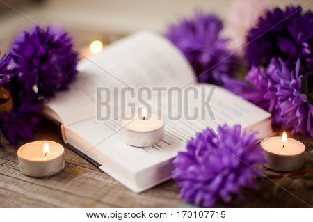 an open book burning candles and purple flowers on wooden background