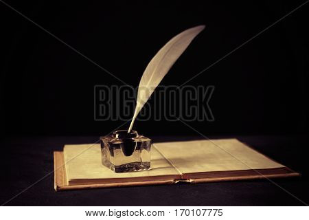 Feather pen with inkwell and open notebook on dark background