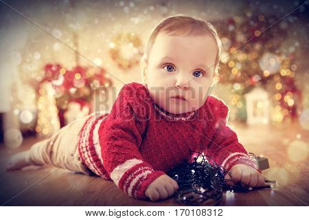 Christmas time. Cute baby crawl on the floor playing with lights. Holiday decorations, Christmas tree