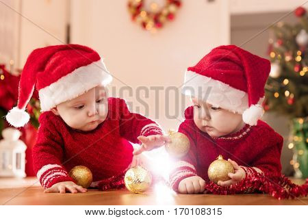 Christmas time. Cute baby twin sisters play with glass balls. Holiday decorations, Christmas tree