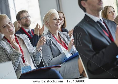 Happy business people applauding during seminar
