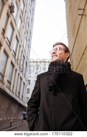 Vertical image of smiling business man in glasses and warm clothes standing on the street and looking away