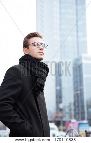 Vertical image of business man in glasses on the street. stands sideways