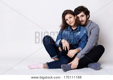 A happy couple sitting crossed legs on the floor. A bearded guy embracing her girlfriend with love. Two people sitting close to each other barefoot isolated over white background