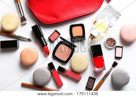 Makeup products with cosmetic bag and macaroons on light background