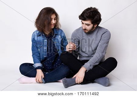 A happy couple sitting on the floor crossed legs holding each other`s hands being happy and pleased to be together. Young bearded man touching his girlfriend`s hand with love. Two young people in love