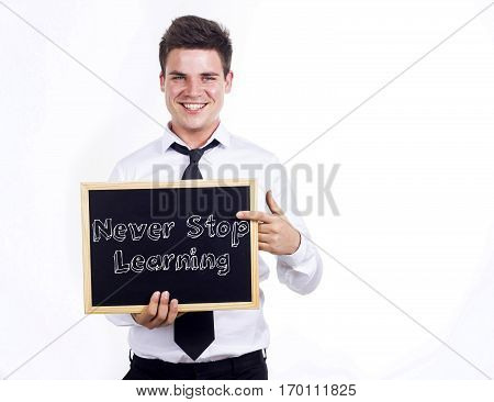 Never Stop Learning - Young Smiling Businessman Holding Chalkboard With Text