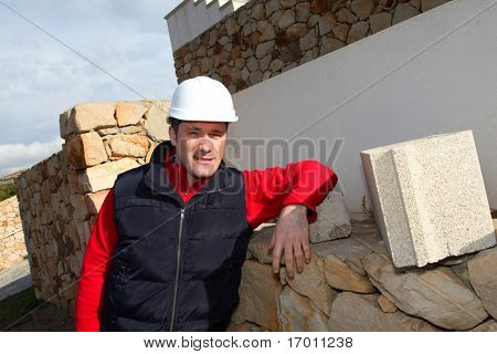 Worker standing in front of house under construction
