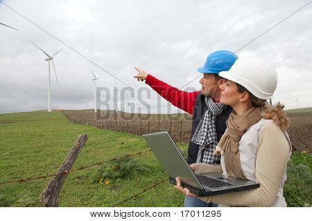 Engineers working by wind turbines field