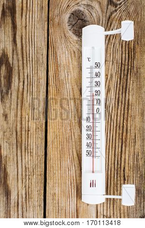 Outdoor thermometer on wood background. Studio Photo