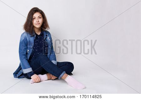 A woman with specific appearance. A woman with dark hair and big brown eyes wearing jeans shirt and jean jacket sitting on the floor crossed legs being happy and relaxed. A shot in white studio