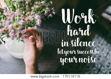 Life quote. Motivation quote on soft background. The hand touching purple flowers. Work hard in silence let your success be your noise.