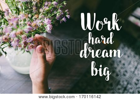 Life quote. Motivation quote on soft background. The hand touching purple flowers. Work hard, dream big