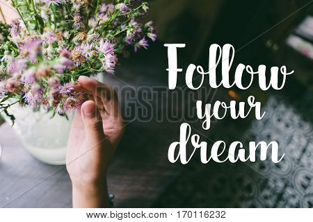 Life quote. Motivation quote on soft background. The hand touching purple flowers. Follow your dream.