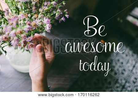 Life quote. Motivation quote on soft background. The hand touching purple flowers. Be awesome today.