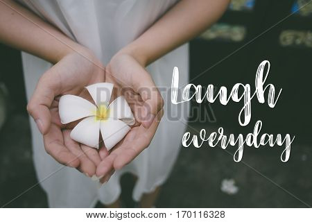 Love quote. Inspirational quote on the girl holding white flower. Laugh everyday.