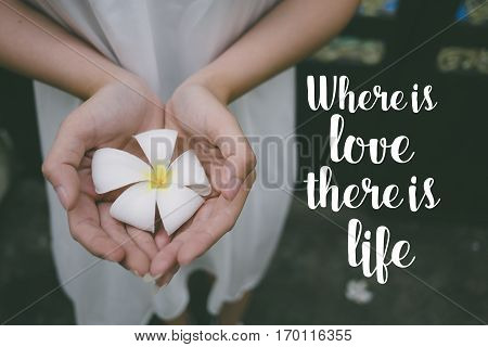 Love quote. Inspirational quote on the girl holding white flower. Where is love there is life.
