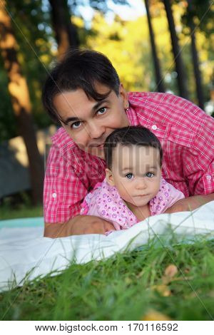 Close up portrait of the cute toddler girl and her father on the grass in the park