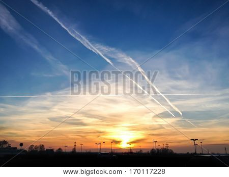 Dramatic sunset with contrails / chemtrails and clouds