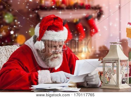 Santa claus reading christmas wish letter against christmas background