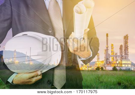 engineering man and safety helmet standing against oil refinery plant in heavy petrochemical industrial estate.