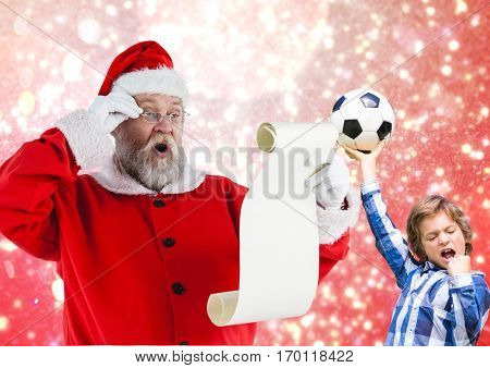 Santa claus reading wish list and excited boy with football against digitally generated background